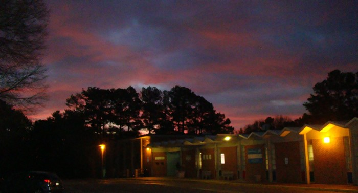 Oakcliff Traditional Theme School front of school on a morning when the sun was just coming up with red clouds in the sky